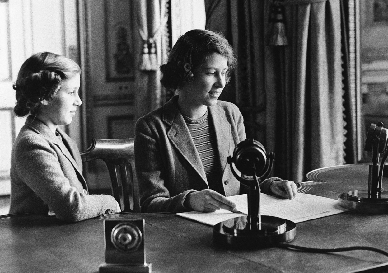 Future queen of britain princess elizabeth giving special radio speech during battle of britain princess margaret next to her