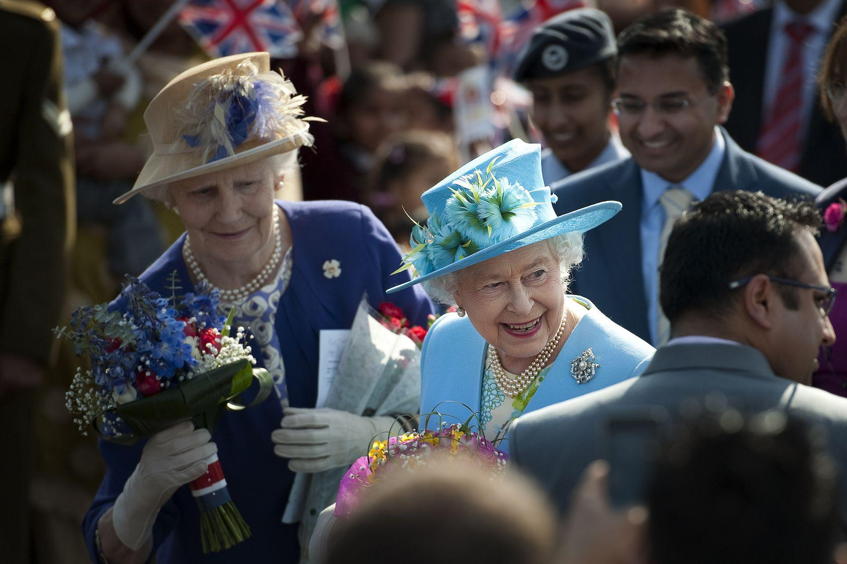 Queen elizabeth with lady in waiting holding flowers 1